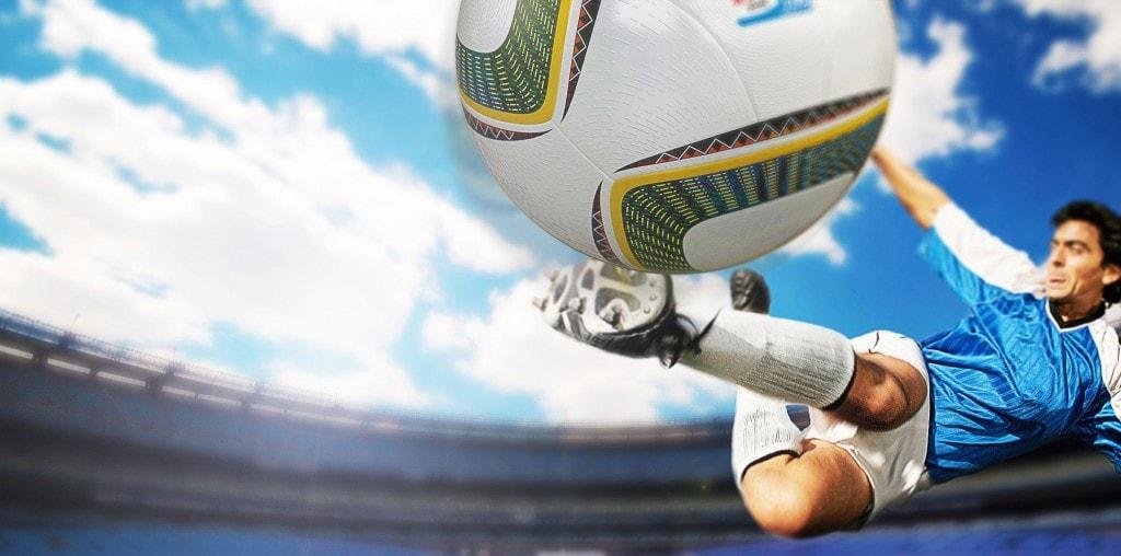 Um jogador de futebol que atinge uma bola